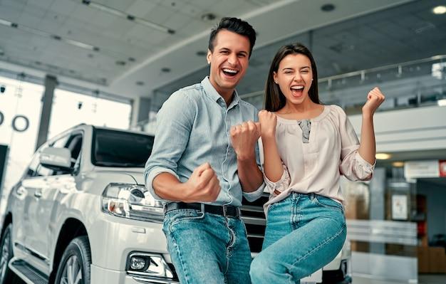 Удачного посещения автосалона. счастливая молодая пара выбирает и покупает новую машину для семьи.