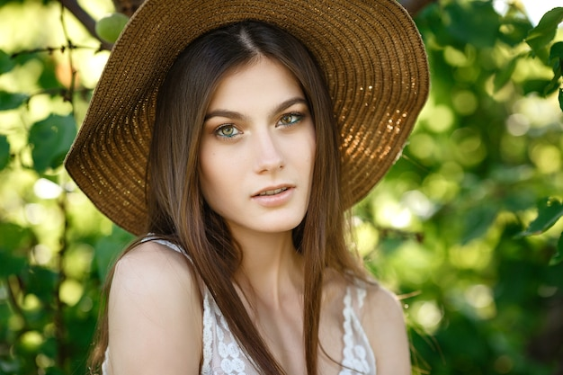 緑の夏の女の子の肖像画。若い美しい黒髪の女性は、夏の庭の涼しさを楽しんでいます。
