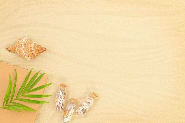 貝殻の本の小さなボトルとビーチの緑の葉と夏の砂浜の背景