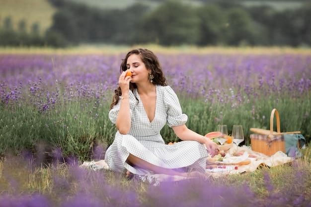 Летний сезон. лавандовые поля. девушка на пикнике среди цветущих полей лаванды. отдых за городом, сельская местность.