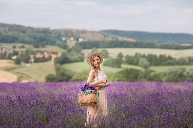Летний сезон. лавандовые поля. девушка с корзиной лавандового поля. сельская местность