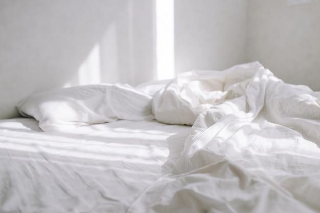 태양은 밝은 침실에서 흰색 시트와 함께 침대에 떨어집니다