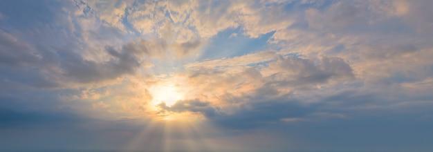 雲のパノラマ写真を通して輝く雲の光線と青い空の太陽