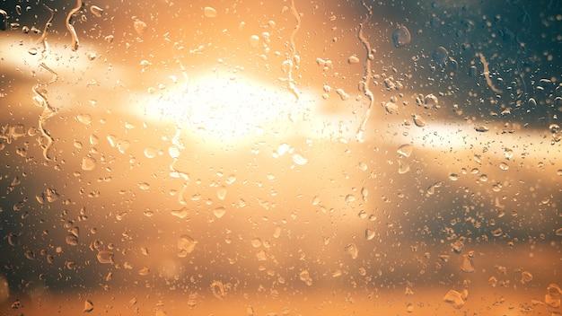 雲の中の太陽が雨の滴のイラストのガラスを通して輝きます