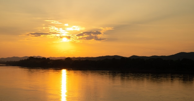 Солнце заходит за горы, вид на красивую реку и пасмурное небо.