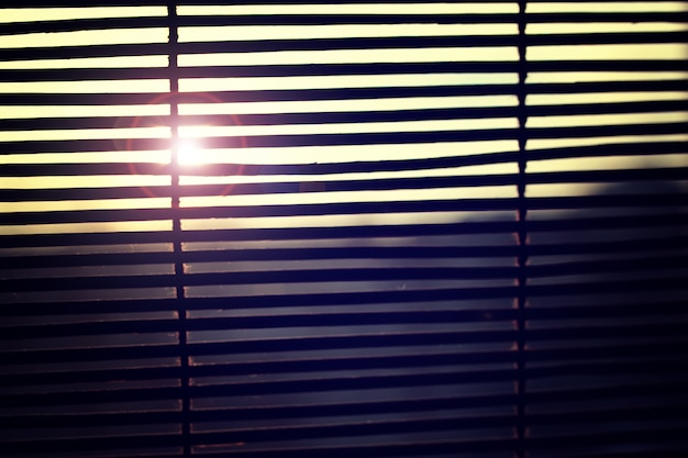 Солнце светит сквозь жалюзи