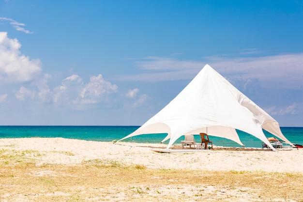 のどかなビーチの大きな日よけの下のサンラウンジャー。ビーチで白いテント。