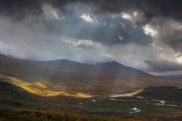 Солнечные лучи пробиваются сквозь темно-серые облака. впечатляющий вид на горы национального парка сарек в шведской лапландии. выборочный фокус