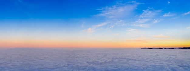太陽の光が雲を暖かく、ピンクと紫の色で照らします