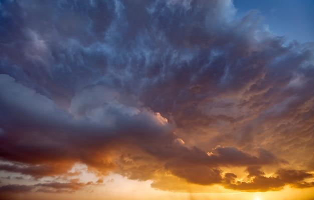 嵐の雲の切れ間から太陽の光が差し込む