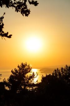 Солнце садится за горизонт на закате над морем или океаном. спокойный океан морских волн. естественное небо в теплых тонах. панорамный вид,