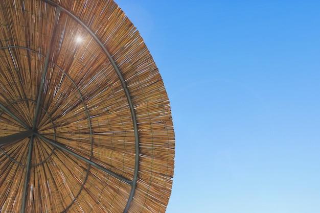 竹の傘を通して太陽が輝いています。わらぶき屋根の背景、干し草または乾草の背景。上からのストロービーチサンシェードビュー。
