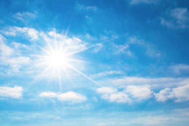 Солнце с яркими лучами в голубом небе с белыми светлыми облаками.