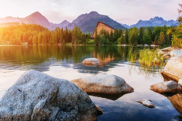 Восход солнца над озером в парке высокие татры. штрбске плесо,