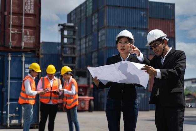 Супервайзер проверяет ящик контейнеров с грузового корабля для экспорта и импорта на фоне группы рабочих.