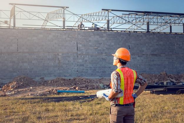 監督者は、計画に従って工事を完了するよう労働者に命じています。