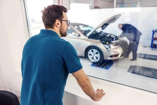 Супервайзер курирует работу в автосервисе. мужчина в синей футболке стоит в офисе, глядя в окно на работника, проводящего технический осмотр автомобиля с поднятым капотом.