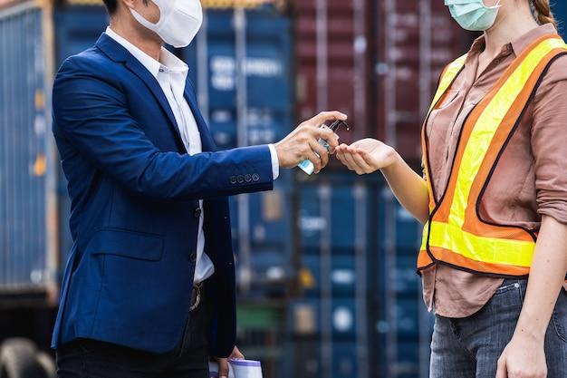 Наблюдатель в защитной хирургической маске прижимает спиртовой гель к коллеге