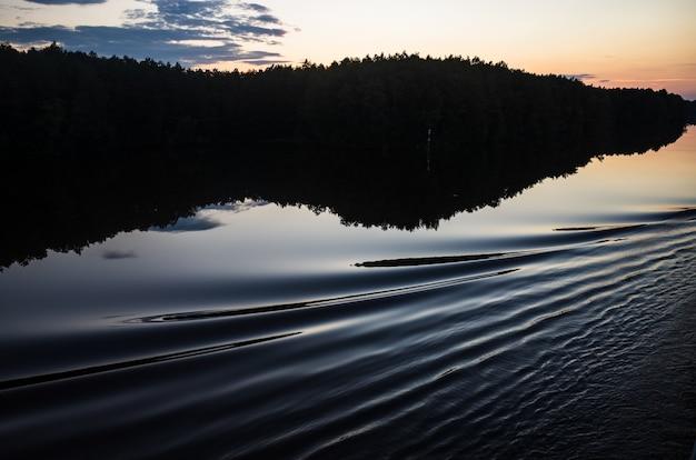 雲と夕暮れの背景に船からの波と穏やかな湖の表面