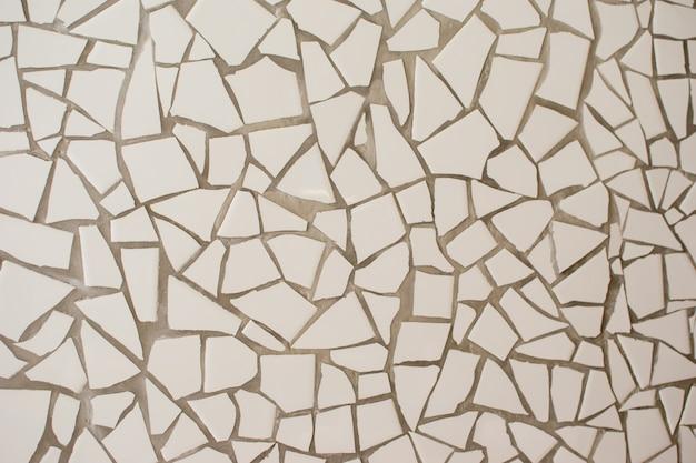 На поверхности много мелких белых плиток разной формы. абстрактная мозаика керамическая плитка с рисунком поверхности. отлично подходит для дизайна и текстуры поверхности.