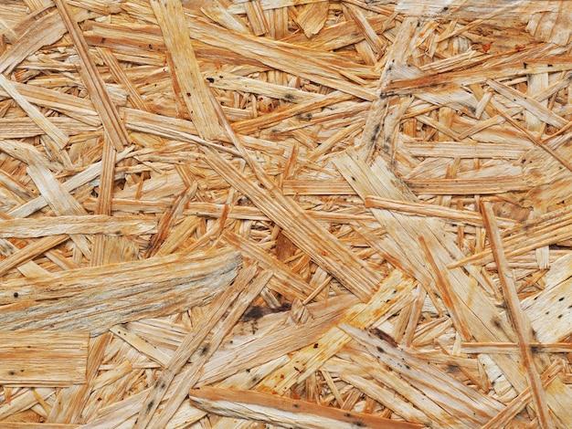 Поверхность прессованной древесины из опилок крупным планом. текстура дсп фон. переработка и повторное использование древесины