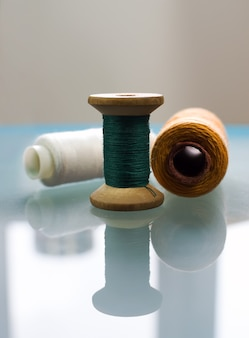 テーブルの表面は、色付きの糸で3つのスプールの反射を作成します