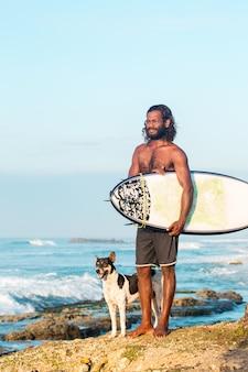 서퍼는 인도양 해안에서 서핑 보드를 들고 있다