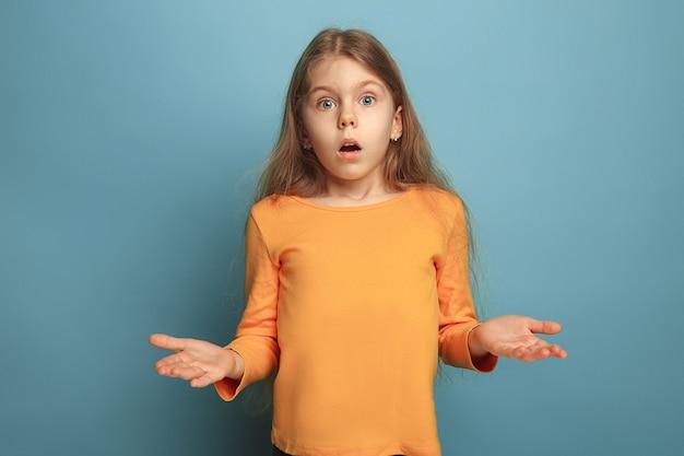 驚き、喜び。青いスタジオで驚いた十代の少女