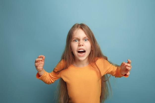 驚き、怒り。ブルースタジオの背景に叫んで驚いて十代の少女。顔の表情と人々の感情の概念。流行色。正面図。半身像