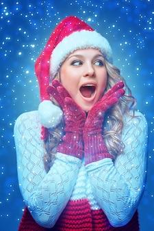サンタの帽子をかぶった驚きの幸せな女の子。青い背景の休日のコンセプトです。