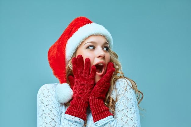 파란색에 산타 모자를 입은 놀라고 행복한 소녀