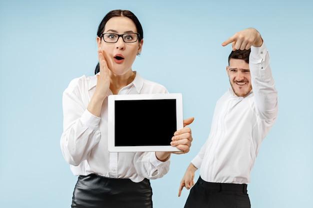 파란색 벽에 웃고 노트북 또는 태블릿의 빈 화면을 보여주는 놀란 비즈니스 남자와 여자