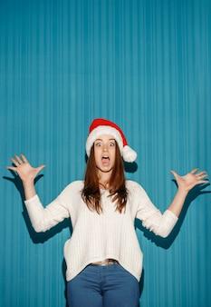 青色の背景にサンタの帽子をかぶっている驚きのクリスマスの女の子