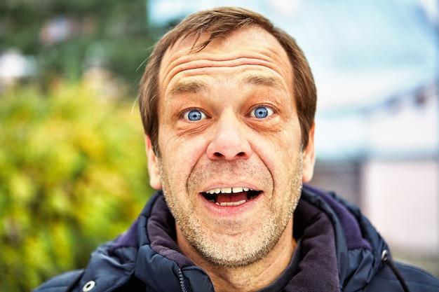 ヨーロッパの通りの壁に向かって50歳の男の驚きの顔。