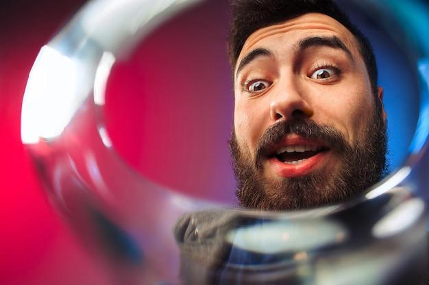Удивленный молодой человек в праздничной одежде позирует с бокалом вина.
