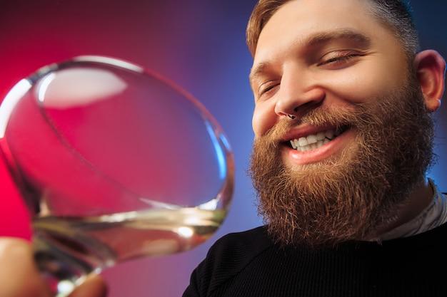Удивленный молодой человек позирует с бокалом вина.