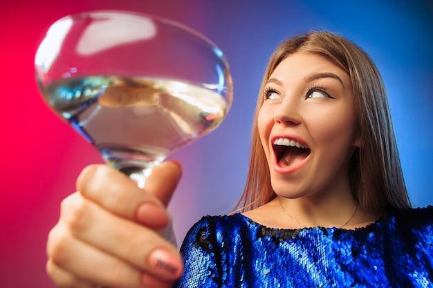 ワインのグラスでポーズをとってパーティー服で驚いた若い女性。感情的な女性のかわいい顔。ガラスからの眺め