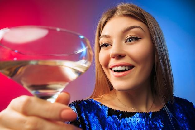 Удивленная молодая женщина в праздничной одежде позирует с бокалом вина