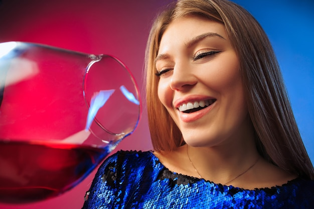 Удивленная молодая женщина в праздничной одежде позирует с бокалом вина.
