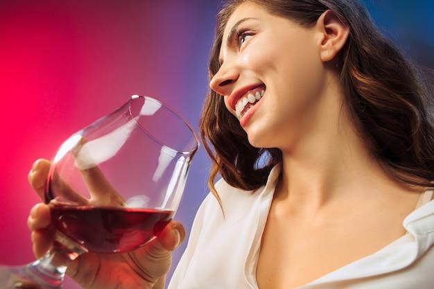 ワインのグラスでポーズをとってパーティー服で驚いた若い女性。