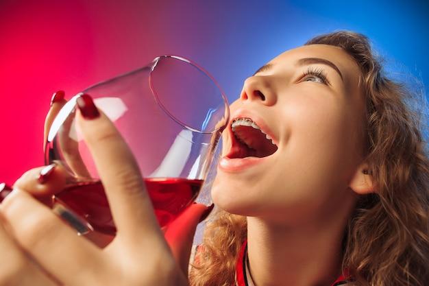 와인 한 잔 함께 포즈 파티 옷에 놀란 된 젊은 여자.