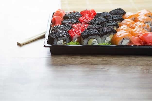 Суши на столе в пакете доставки, заказанные в суши-ролле.