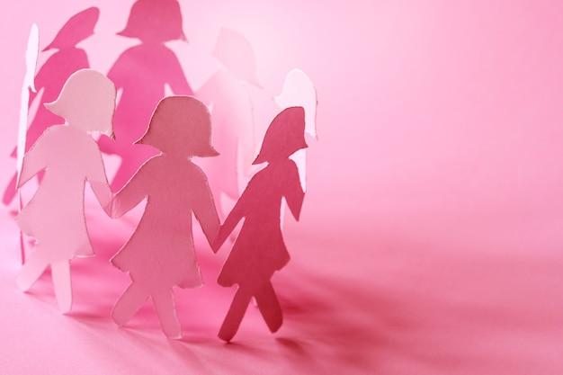 ピンクの背景に甘いピンクの女の子の紙の人形