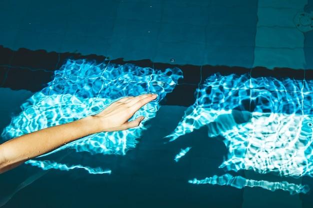 수영 선수의 손이 밝은 햇빛이 비추는 푸른 투명한 맑은 물이있는 물 웅덩이로 뛰어 들었습니다.