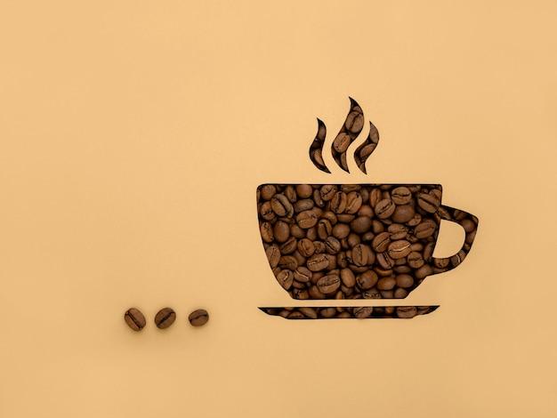 シンボルは黒い芳香のコーヒー豆のカップです。紙の背景、切り抜き、スペースとテキスト用のスペースのコピー