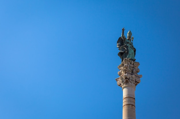 レッチェの町(イタリア)のシンボル:メインタウン広場の中央の柱に置かれた聖オロンゾ(sant'oronzo)。コピースペースのある青い背景。