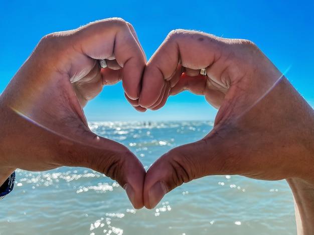 사랑, 바다에 대한 사랑, 여행 및 여름 휴가를 상징하는 두 손으로 만든 하트의 상징.