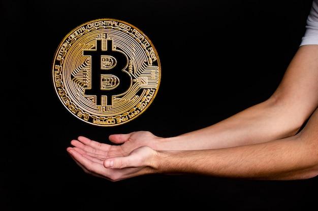 手のイメージを持つ新しい人気の暗号通貨ビットコインのシンボル