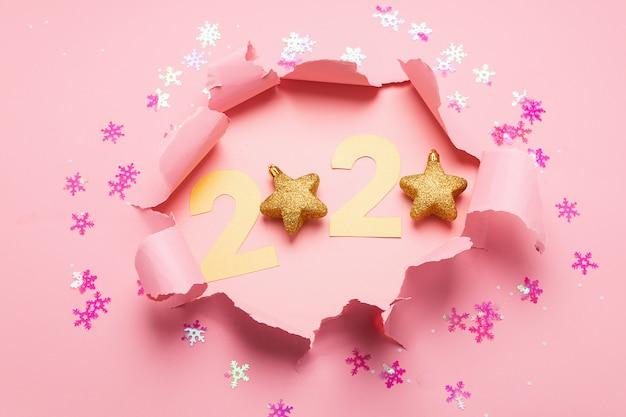 숫자 2020에서 새해의 상징이며 분홍색 종이 배경에 구멍이 있습니다.