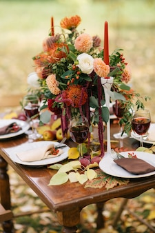 가을 정원에서 꽃과 촛불로 장식 된 테이블